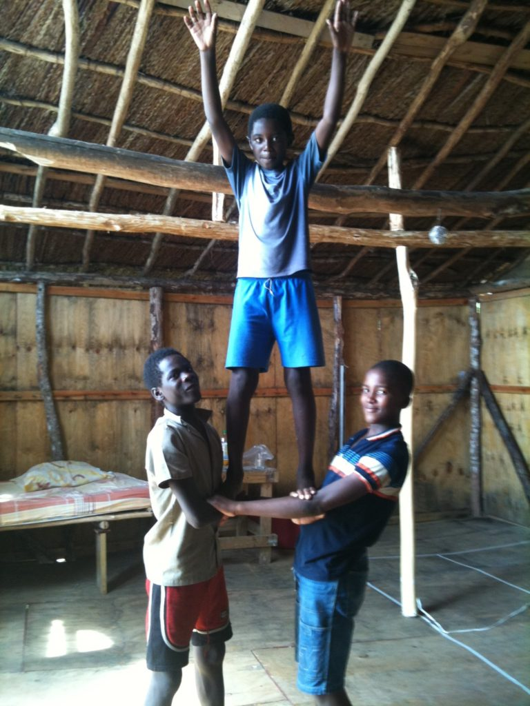Three boys form a human triangle