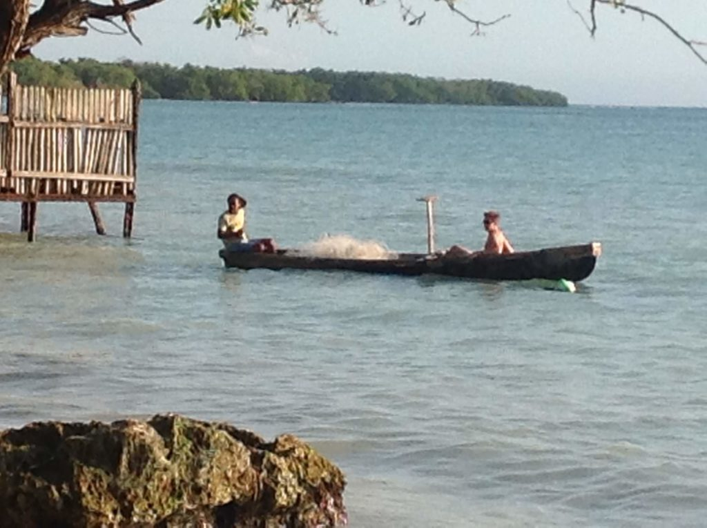 Two people sit in a canoe near a dock on the sea.