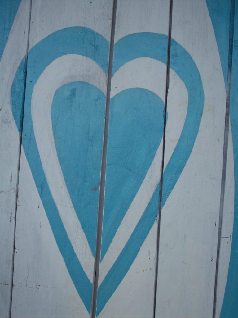 A blue heart painted on wood panels