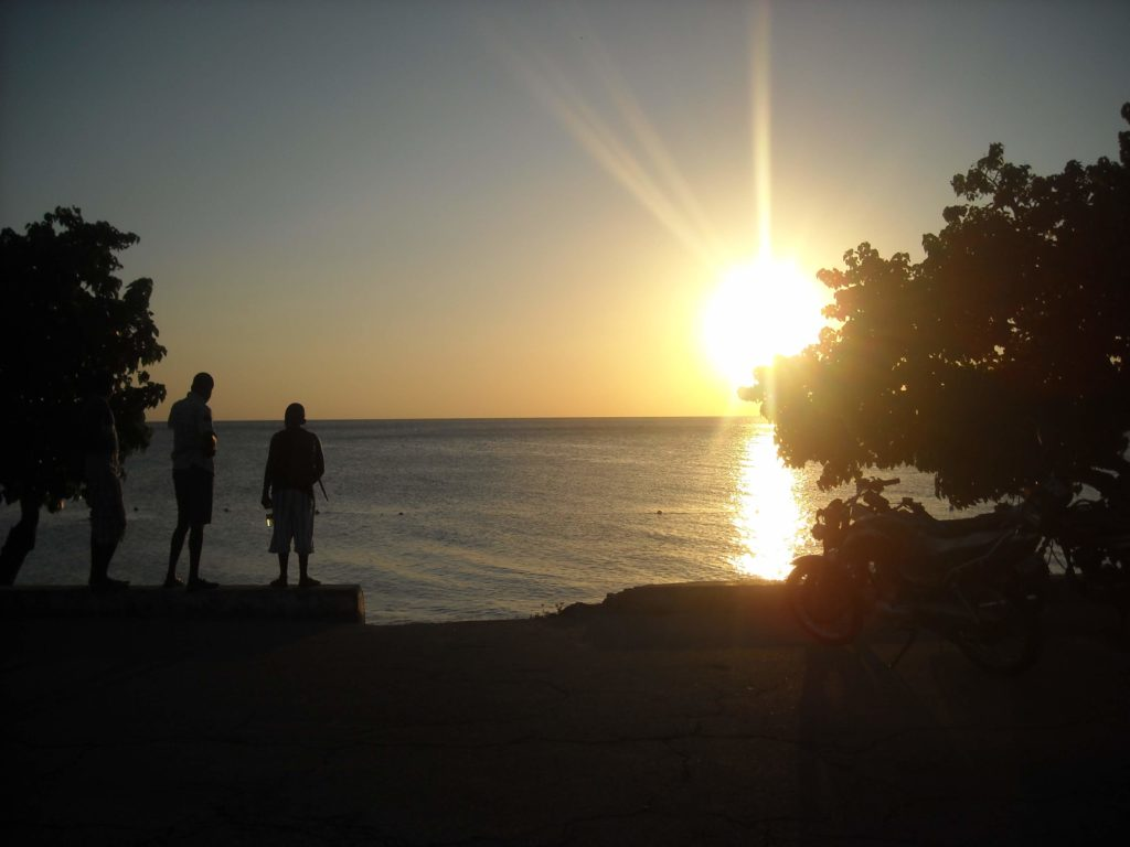 Two silhouetted figures stand in front of an ocean sunset