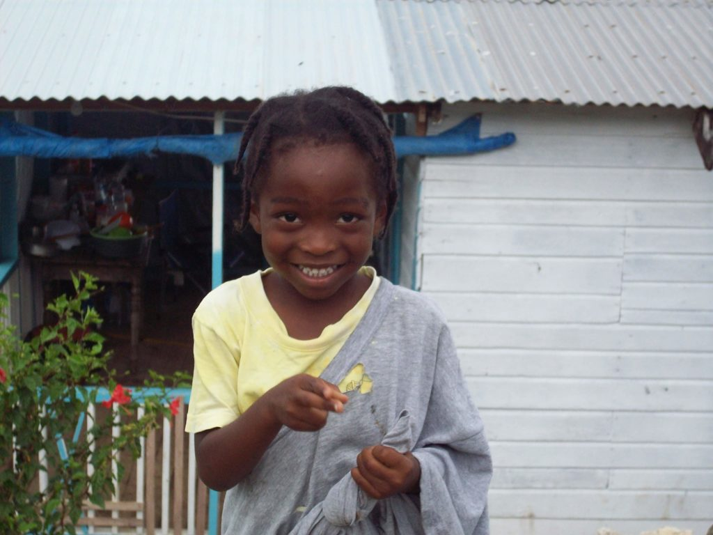 A little Jamaican boy smiles big for the camera
