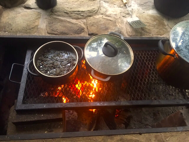 Pots cooking food over the outdoor fire
